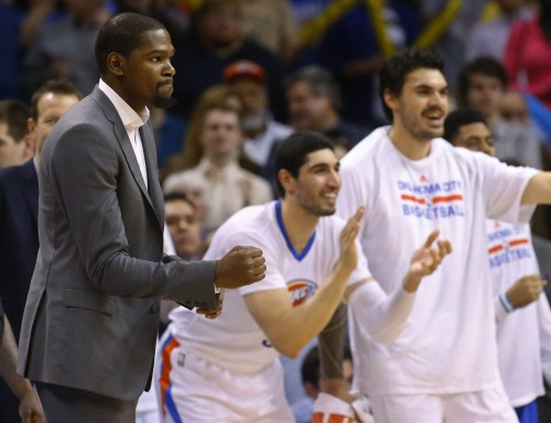 Injured Oklahoma City Thunder forward Kevin Durant, left, pumps his fist at teammates Enes Kanter, center, and Steven Adams, right, cheer in the fourth quarter of an NBA basketball game against the Toronto Raptors, Sunday, March 8, 2015, in Oklahoma City. Oklahoma City won 108-104. (AP Photo/Sue Ogrocki)